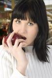 Beau jeune femme mangeant Apple Photographie stock libre de droits