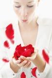 Beau, jeune femme soufflant les pétales de rose rouges de ses paumes Photographie stock libre de droits