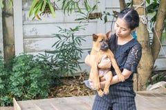 Beau jeune heureux de femme avec le chien thaïlandais de ridgeback dans la main de parc tenant le petit chien Photographie stock