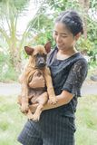 Beau jeune heureux de femme avec le chien thaïlandais de ridgeback dans la main de parc tenant le petit chien Photo libre de droits