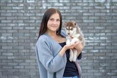 Beau jeune heureux de jolie femme avec de longs cheveux sombres tenant le petit chiot de chien sur le fond de ville de rue Photos stock