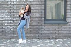 Beau jeune heureux de jolie femme avec de longs cheveux sombres tenant le petit chiot de chien sur le fond de ville de rue avec l Images libres de droits