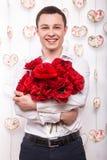Beau jeune homme dans l'amour avec un bouquet des fleurs Le jour de Valentine Photographie stock libre de droits