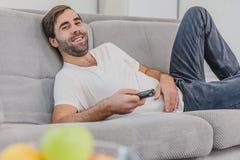 Beau jeune homme hilare tenant un à télécommande Pendant ce temps il regarde la caméra, sourires tout en se reposant dessus photo stock