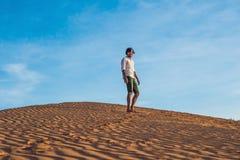 Beau jeune homme sautant nu-pieds sur le sable dans apprécier de désert photos stock
