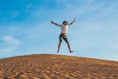 Beau jeune homme sautant nu-pieds sur le sable dans apprécier de désert photos libres de droits