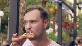 Beau jeune mangeur d'hommes une tranche de pizza en café plan rapproché, 4k, au ralenti banque de vidéos