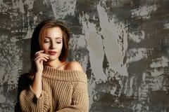 Beau jeune modèle utilisant le chandail tricoté avec l'épaule nue, posant avec des ombres L'espace vide photographie stock