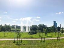 Beau jeune parc vert au centre d'une grande ville avec des fontaines et des jeunes plantes de petits arbres sur le fond image libre de droits