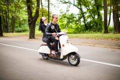 Beau jeune scooter d'équitation de couples ensemble, femme étreignant son ami Vue de côté sur la vitesse Images libres de droits