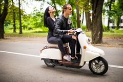 Beau jeune scooter d'équitation de couples ensemble, femme étreignant son ami Vue de côté sur la vitesse Photo stock
