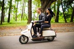 Beau jeune scooter d'équitation de couples ensemble, femme étreignant son ami Vue de côté sur la vitesse Photographie stock libre de droits