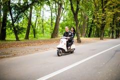 Beau jeune scooter d'équitation de couples ensemble, femme étreignant son ami Vue de côté sur la vitesse Image stock