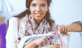 Beau jeune styliste près de support avec des cintres photo libre de droits