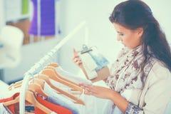 Beau jeune styliste près de support avec des cintres dans le bureau Images libres de droits