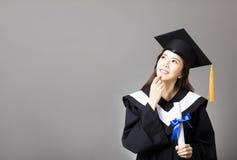 Beau jeune universitaire tenant le diplôme et la pensée photo stock