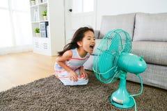 Beau jeune visage d'enfants féminins au ventilateur électrique Photo stock