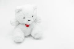 Beau jouet blanc d'ours de nounours se reposant avec le coeur rouge sur le fond blanc Photographie stock