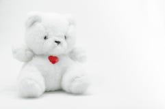 Beau jouet blanc d'ours de nounours se reposant avec le coeur rouge sur le fond blanc Images libres de droits
