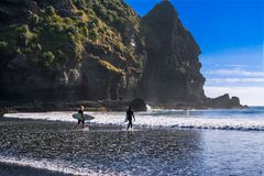 Beau jour à la plage de Piha Jeunes surfers se dirigeant dans l'eau photographie stock libre de droits