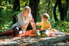 Beau jour pour le pique-nique de ressort en nature Explorez la nature ensemble Gar?on de maman et d'enfant d?tendant tout en augm images stock