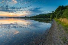 Beau lac au paysage de coucher du soleil avec le ciel nuageux se reflétant dans l'eau Photographie stock libre de droits
