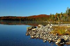 beau lac de plage au-dessus de lever de soleil pierreux Photos stock