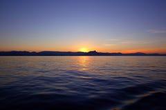 Beau lever de soleil au-dessus de ciel bleu de rouge d'océan de mer Images libres de droits
