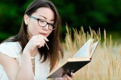 Beau livre de lecture coréen de fille dehors photographie stock