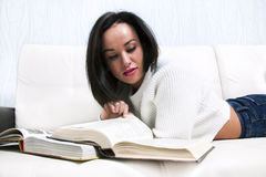 Beau livre de lecture de jeune fille se trouvant sur le divan photographie stock