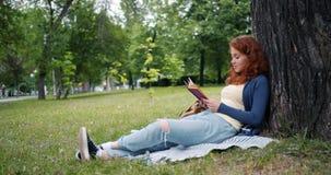 Beau livre de lecture de jeune femme se reposant sur la couverture sous l'arbre dans le sourire de parc banque de vidéos
