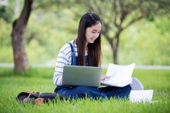 Beau livre et fonctionnement de lecture asiatique de sourire de fille à l'arbre dessus photographie stock libre de droits
