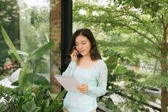 Beau livre ou journal intime asiatique heureux de participation de femme sur le fond ext?rieur naturel vert photo libre de droits
