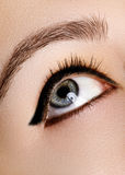 Beau macro tir d'oeil femelle avec le maquillage Forme parfaite des sourcils, eye-liner bleu Produits de beauté et renivellement Photographie stock
