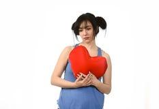Beau mal de femme et souffrance pour l'amour perdu tenant l'oreiller rouge de forme de coeur Photos stock