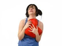 Beau mal de femme et souffrance pour l'amour perdu tenant l'oreiller rouge de forme de coeur Image stock
