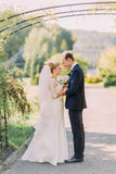 Beau marié et jeune mariée de jeunes se regardant le jour du mariage Parc ensoleillé d'été sur le fond Photo libre de droits