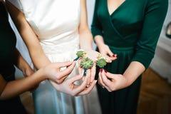 Beau mariage boutonier avec les fleurs vertes dans les mains de la jeune mariée et des amies, matin de la jeune mariée Photo libre de droits