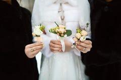Beau mariage sensible boutonier avec les fleurs crémeuses et blanches dans les mains de la jeune mariée et des amies Photographie stock libre de droits