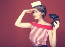 Beau marin de fille avec des jumelles d'un vintage et examinations la distance Photographie stock