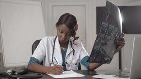 Beau membre du personnel soignant d'afro-américain avec le rayon X, concept international médical, pensée noire de docteur, moder clips vidéos