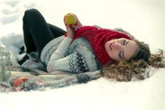Beau, mignon, heureux, léger, fille se trouvant sur une couverture pendant l'hiver dans la neige Photos stock