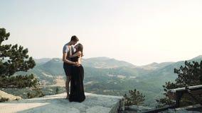 Beau modèle affectueux de jeune femme de couples dans une longue robe intelligente et un homme dans un costume noir posant sur l' banque de vidéos