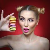 Beau modèle avec le maquillage et la coiffure créative tenant les macarons colorés, pousse de studio sur le fond rouge Photographie stock libre de droits