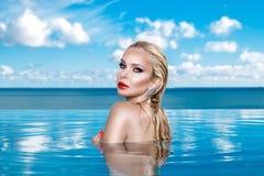 Beau modèle blond de femme avec les cheveux humides et le maquillage élégant se reposant dans une piscine Photographie stock