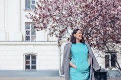 Beau modèle dans la robe bleue et le manteau gris par l'arbre de floraison de ressort photographie stock libre de droits