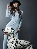 Beau modèle dans un chapeau avec le beau maquillage et un chien dalmatien Photos libres de droits
