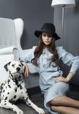 Beau modèle dans un chapeau avec le beau maquillage et un chien dalmatien Photo stock