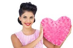 Beau modèle de cheveux noirs tenant un oreiller en forme de coeur rose Photo libre de droits
