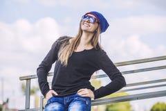 Beau modèle de femme dans le chapeau et des lunettes de soleil dans la ville Photo stock